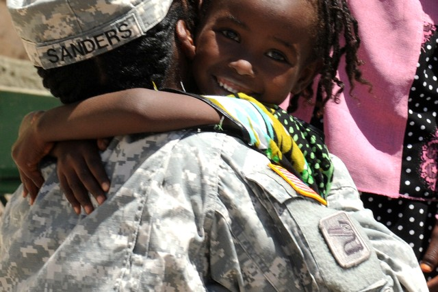 Capt. Courtney Sanders, 402nd Civil Affairs Battalion, makes friends with a young girl at Dikhil High School April 19, 2011.