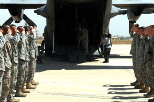 Soldiers salute wounded warriors exiting the aircraft as part of Operation Proper Exit, April 25, 2011, at Sather Air Base, Iraq. These veterans are returning to Iraq to look for a sense of closure and a proper exit.