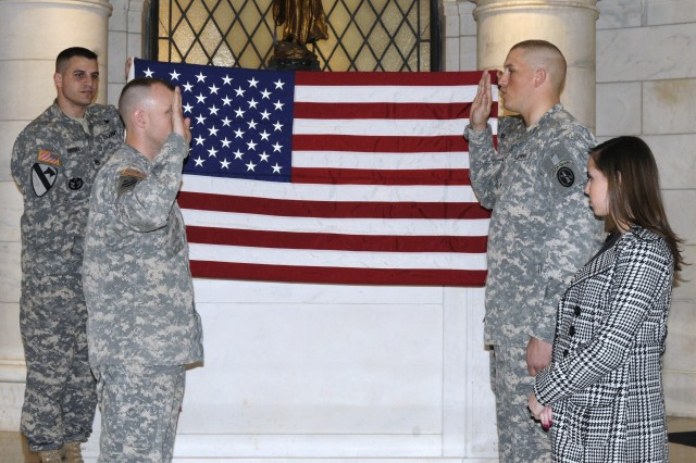 Spc. Mathew Brisiel (right) Sentinel at the Tomb of the Unknown Soldier, 3d U.S. Infantry Regiment (The Old Guard) repeats the reenlistment oath as his brother, Staff Sgt. Jonathan Brisiel, (top left)1st Battalion, 3d Inf. Reg. Career Counselor, holds the U.S. flag. Jonathan reenlisted his younger brother after recently becoming a career counselor. (Photo by Sgt. Erica Vinyard)