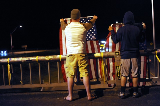 Spc. Mark Anderson, 61st Chem. Bn., left, and Staff Sgt. Lemuel Nacionales, MAMC, hold flags from 'Freedom Bridge' above Interstate 5 outside the Madigan Gate at Joint Base Lewis-McChord May 1, 2011 in celebration of the death of Al Qaeda leader Osama bin Laden. (Ingrid Barrentine/Northwest Guardian)