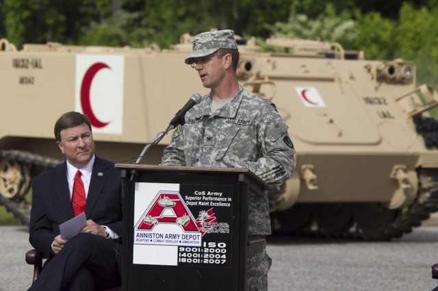 Depot Commander Col. Timothy Sullivan welcomes the audience at the M113 FOV/M88 Iraq FMS Rollout Ceremony on April 28, held in the Nichols Industrial Complex. Looking on is one of the keynote speakers, Congressman Mike Rogers, Alabama's 3rd Congressional District. Shown behind is a M113A2 ambulance.
