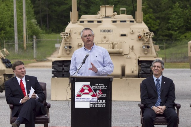 Michael Burke, general manager of production operations, speaks at the M113 FOV/M88 Iraq FMS Rollout Ceremony held April 28. Pictured (l to r) Cong. Mike Rogers, 3rd Congressional District and Gilbert Liptak, director of TACOM's Security Assistance Management Directorate.