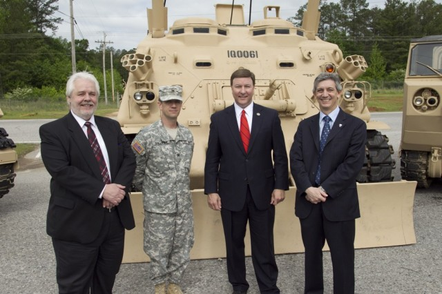 Posing with depot commander, Col. Timothy Sullivan in front of an M88A1 vehicle are Dave Carter, TACOM ILSC; Congressman Mike Rogers, 3rd Congressional District; and Gilbert Liptak, director, TACOM SAMD.