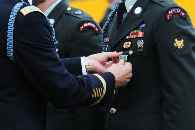 Lt. Col. Dave Hodne, the commander of 2nd Battalion, 75th Ranger Regiment on Joint Base Lewis-McChord, Wash., pins an Army Commendation Medal on one of the battalion's Soldiers April 29 during an award ceremony at Stadium High School in Tacoma to recognize the valorous combat actions of 46 members of the battalion, though some could not be present. The event marked the very first award ceremony the battalion has ever held off-post and in a public setting.