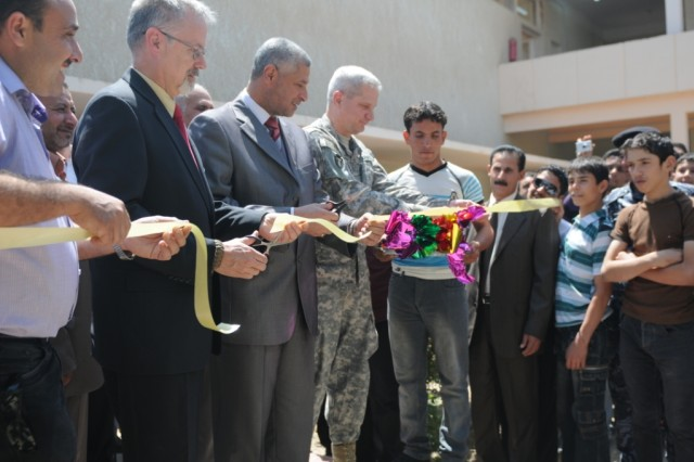 Brig. Gen. Stephen Sanders, deputy commander of support for U.S. Division - South and the 36th Infantry Division, along with Samuel Madsen, the Wasit Provincial Reconstruction Team leader, and Iraqi officials, cuts a ceremonial ribbon at the official opening of the Al-Aziziyah school in Iraq's Wasit province, April 27.