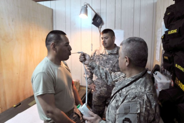 BASRAH, Iraq - Staff Sgt. Luis Vegamaldonado, a medic with the 36th Infantry Division, gets a temperature reading on Sgt. Juan Arriaga, an infantryman also with the 36th Inf. Div. Vegamaldonado, of Round Rock, Texas, performed the checkup on Arriaga to he was able to return to duty after having the flu.