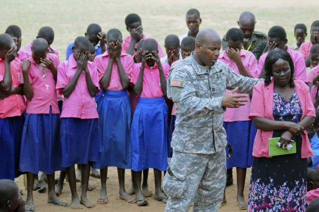 Chaplain (Capt.) Andy Shepherd of Moreland, Ga., 3rd Squadron, 108th Cavalry Regiment, Georgia National Guard, prays for the school children of the Ududui Primary School near Soroti, Uganda, April 15, 2011, during an outreach visit during Atlas Drop 11.