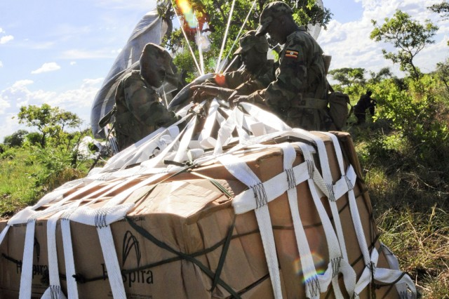 Uganda People's Defense Forces Soldiers work to free supplies dropped from a C-17 aircraft via a Low Cost Aerial Delivery system at Drop Zone White near Olilim, Uganda, April 18, 2011, during Atlas Drop 11.