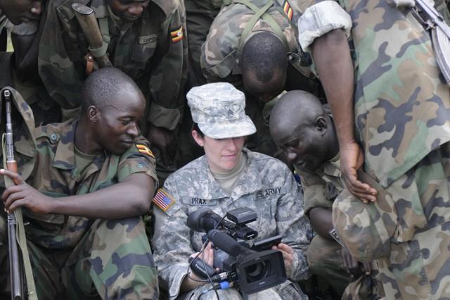 Ugandan People's Defense Forces soldiers crowd around Sgt. Lyndsey Prax, a U.S. Army Utah National Guard videographer, during Atlas Drop 11, April 14, 2011.