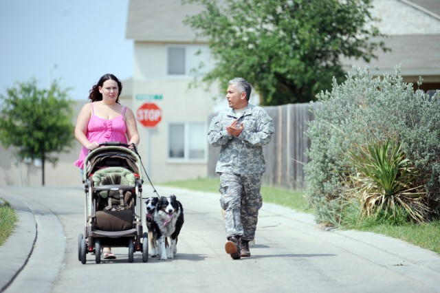 Cesar Millan walks with Ciarra Walker and dogs Maggie and Patches, April 19, 2011, in Kouma Village at Fort Hood, Texas. Millan is highly regarded for his ability to understand dogs.