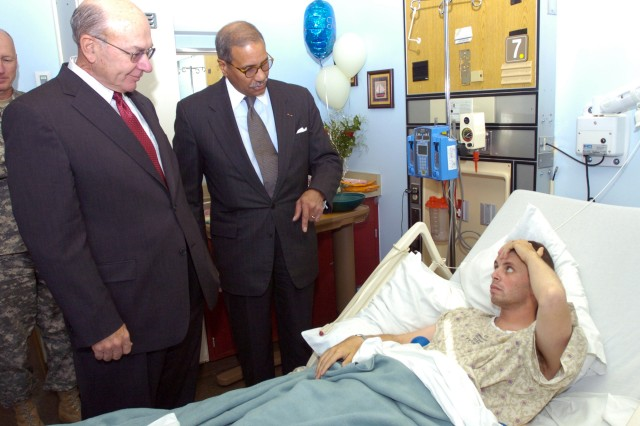 Spc. Matthew Cooke receives a surprise visit from former Chief of Naval Operations retired Adm. Vernon Clark and former Secretary of the Army Togo West, while recovering from bullet wounds received during the Nov. 5, 2009, shooting at Fort Hood, Texas.
