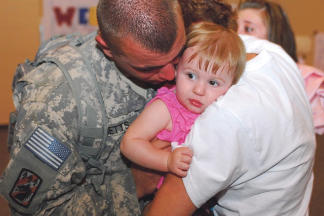 Pvt. Robert Betts hugs his mom, Donna, and 1-year-old daughter, Autumn, after returning Wednesday from a yearlong deployment to Afghanistan. Taking over the company\'s Kandahar mission is the South Carolina National Guard's 742nd Maintenance