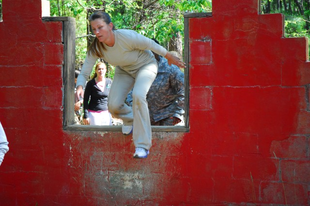 Brook Willis leaps over a wall on the Fit to Win course. Throughout the day spouses got to experience typical Basic Combat Training events, such as obstacle courses and basic rifle marksmanship exercises.