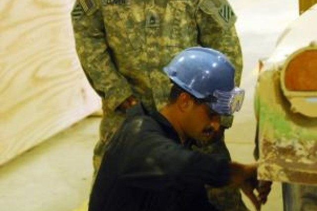 Sergeant First Class Andre Oliver, B Co., 703rd BSB, 4th AAB, 3rd ID, looks on as an Iraqi army mechanic replaces a Humvee tire during a maintenance rodeo competition at Al Asad Air Base, Iraq, April 27.