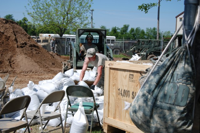 Soldiers work to move recently filled sandbags at a Missouri National Guard sandbagging operation in Sikeston, Mo. Soldiers worked at the site with a sandbag filling machine provided by the U.S. Army Corps of Engineers. The Corps of Engineers also provides sandbags to help combat flooding and to date the Corps' Memphis has issued nearly 2 million sandbags for communities within its area of operations to help with this year's historic floodfighting efforts.