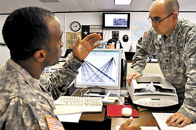 Staff Sgt. Paul Roberts (left) discusses the call-pattern organizational chart on his computer screen with another Soldier at the Drug Enforcement Administration office in San Antonio.