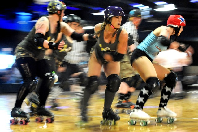 "GI Janes' Patty Jean King, center, or ""PJ Ruckus"" winces as she tries to keep Bombshell Betties jammer Sarah Howard, right, aka ""Gloria Sass"" out of the lead position during the Battle of Derby Hill roller derby bout April 30 at"