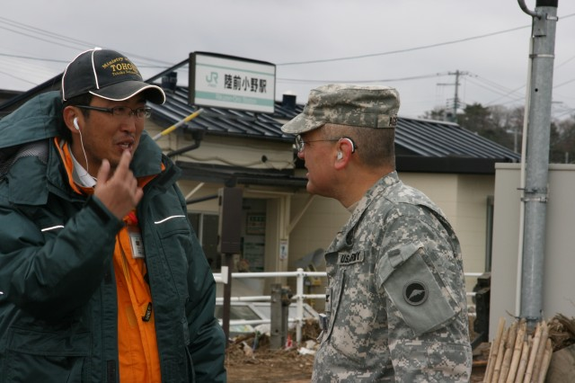 Col. Craig J. Agena, chief of the bilateral coordination action team U.S. contingency at Camp Sendai, talks with a Japanese official at the Rikuzen-Ono train station, Higashi Matsushira, Japan in order to help facilitate operations set to clear wreckage and debris as part of a U.S. and Japanese combined effort to restore local transportation.