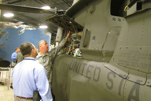 Chief Warrant Officer 4 Andrew Diener of the Corpus Christi Army Depot shows Bill Doty of Avion some of the new engine parts that have brought new life to a crashed OH-58D Kiowa helicopter. The helicopter was repaired at the depot in a program supported by AMCOM and its partners.
