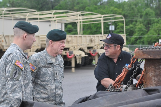 Colonel Mark Mitchell, 5th Special Forces Group commander, and Command Sgt. Maj. Michael Cunningham, 5th SFG deputy CSM, take a moment to talk to Denton Carr, Landstar Trucking, as he reveals the steel he transported from New York City. The New York City Port Authority sent the remnants from the World Trade Center to the 5th SFG as a thank you for the role they played in combating terrorism around the world after 9/11.