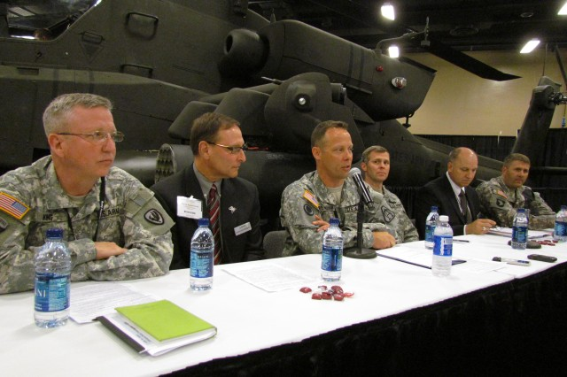 Col. Shane Openshaw provides media with production updates during an Apache media roundtable at the Aviation Association of America annual Professional Forum and Exposition on April 18. To the far right is Lt. Col. Hank Taylor, who gave media a picture of the Apache's effectiveness as a game changer on the battlefield. An Apache helicopter is in the background.