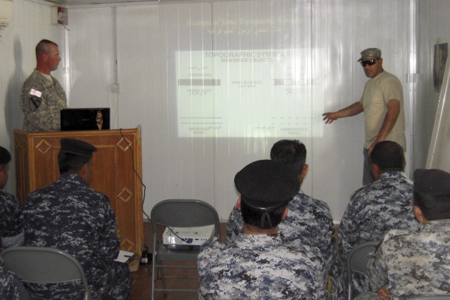 """BAGHDAD-Staff Sgt. Jason Beaudre, a platoon sergeant with B Troop, 6th """"Saber"""" Squadron, 9th Cavalry Regiment, 2nd Advise and Assist Brigade, 1st Infantry Division, United States Division - Center and his interpreter teach map reading course to members of 1st Mechanized Brigade on April 25, 2011."""