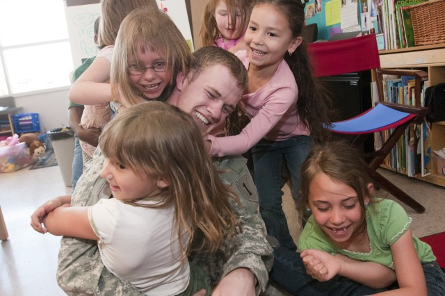 Sgt. Brandon Petry, a Soldier from Fort Riley's Combat Aviation Brigade, 1st Infantry Division, is surrounded by children from Wamego's Central Elementary School during an indoor recess, May 5. Petry and several other Soldiers from the brigade's 2nd General Support Aviation Battalion, 1st Aviation Regiment visited the school as part of an Adopt-a-School program. The battalion has sent Soldiers to the school to interact with the students and help at school events since January. (U.S. Army photo by Sgt. Roland Hale, CAB, 1st Inf. Div. PAO)