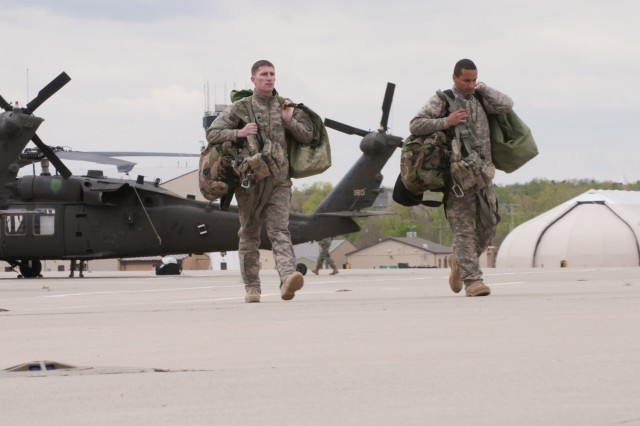 Black Hawk crew chiefs with Fort Riley's Combat Aviation Brigade, 1st Infantry Division carry gear from their aircraft, April 27. The brigade's aircraft are returning to Fort Riley this week after a year in Iraq.  (U.S. Army photo by Sgt. Roland Hale, CAB, 1st Inf. Div. PAO)