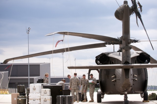 Soldiers with Fort Riley's Combat Aviation Brigade, 1st Infantry Division unload a Black Hawk helicopter on Marshall Army Airfield, April 27. Following a year in Iraq, the brigade's aircraft are returning to the airfield this week. (U.S. Army photo by Sgt. Roland Hale, CAB, 1st Inf. Div. PAO)