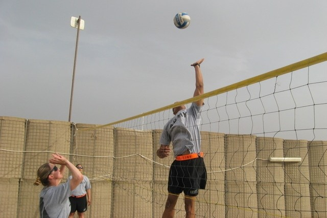 Contingency Operating Base Basrah, Iraq - Pfc. Brandon Combs prepares to execute a spike on Spc. Christina Henderson during the volleyball portion of the Alpha Distribution Company, 215th Brigade Support Battalion, 3rd Brigade Combat Team, 1st Cavalry Division Organizational Day.