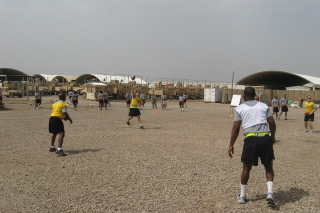 Contingency Operating Base Basrah, Iraq - Sgt. Alejandro Cosme throws a touchdown pass in the Ultimate Football competition, part of the Alpha Distribution Company, 215th Brigade Support Battalion, 3rd Brigade Combat Team, 1st Cavalry Division, Organizational Day.