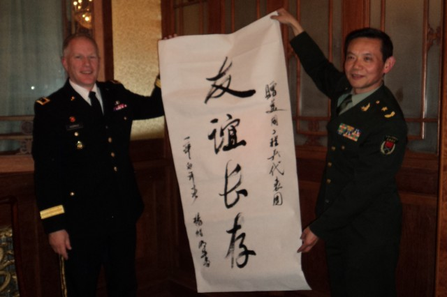 Maj. Gen. Jeffrey J. Dorko, deputy commanding general for Military and International Operations for the U.S. Army Corps of Engineers, accepts a traditional script, which signifies trust and partnership through cooperation, from People's Liberation Army Maj. Gen. Yang Xu Ming, deputy director, Training and Arms Department.
