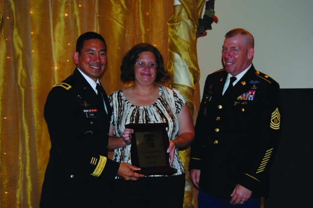 Joint Readiness Training Center and Fort Polk commanding general Brig. Gen. Clarence K. K. Chinn (left), and Command Sgt. Maj. Jeffery Hof, post command sergeant major, present Bridget Payne the 2011 Volunteer of the Year Award May 2 at the Fort Polk Volunteer Award Ceremony at Warrior Community Center.