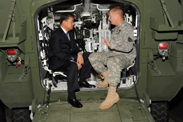 Retired Gen. Eric K. Shinseki sits inside a Stryker vehicle and talks with Col. Robert Schumitz, Stryker project manager, about how the vehicle was first fielded 10 years ago as the Interim Armored Vehicle.