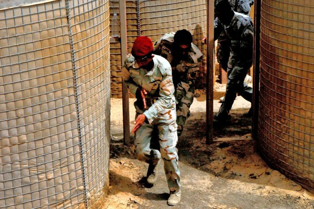 Soldiers with the 6th Iraqi Army Division practice entering and clearing a room inside a training course built out of barriers at Joint Security Station Constitution. The training was led and observed by B Company, 1st Battalion, 63rd Armor Regiment, 2nd Advise and Assist Brigade, 1st Infantry Division, U.S. Div. - Center.
