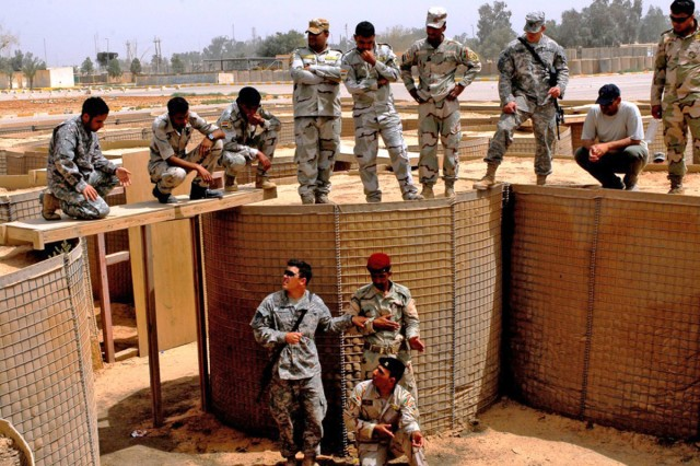Sgt. Andrew Drake, bottom left, a team leader with B Company, 1st Battalion, 63rd Armor Regiment, instructs Iraqi Army soldiers with the 6th Iraqi Army Division on how to handle the situation when a soldier's weapon malfunctions during a room-clearance procedure.