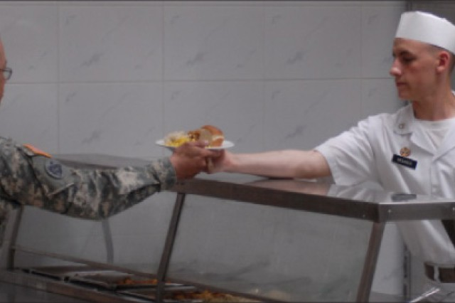 Pfc. Tim Mourer serves dinner to a Soldier at the newly constructed Daegu Mountain Inn Dining Facility on Camp Walker.