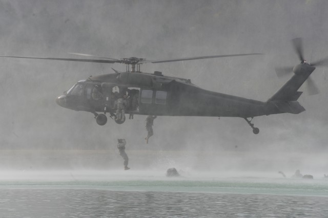 Participants in the 2011 Best Sapper Competition jump out of a UH-60 Black Hawk helicopter during the helocast and swim portion on the first day of the competition, at Fort Leonard Wood, Mo.