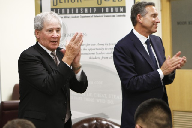 Bill Campbell, Intuit, Inc. chairman of the board (left), joins Starbucks CEO Howard Schultz in a round of applause for the cadets at the Black and Gold Leadership Forum. Campbell said it was a humbling experience talking with cadets on leadership at West Point.