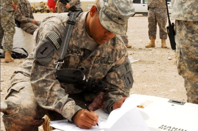 Spc. Entoinne Johnson, a supply sergeant serving with 1st Advise and Assist Task Force, places condition codes on forms necessary to turn in his unit's unserviceable equipment at Contingency Operating Site Warrior, Iraq. Johnson said he uses the codes to explain what needs to be done to the item before it reaches its final destination.