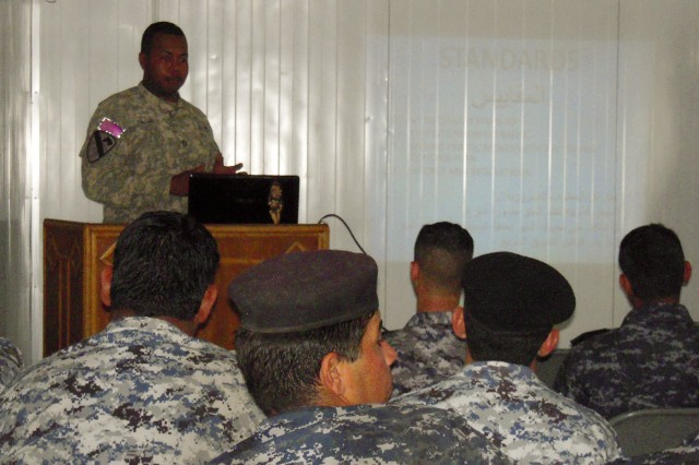 """BAGHDAD—Staff Sgt. Cedric Wilson of Bandit Troop, 6th """"Saber"""" Squadron, 9th Cavalry Regiment, 2nd Advise and Assist Brigade, 1st Infantry Division, United States Division – Center, and a native of Leesville, La., with assistance of a translator, teaches basic traffic control point operations during the classroom portion of the training to Soldiers of 1st Mechanized Brigade on May 2."""