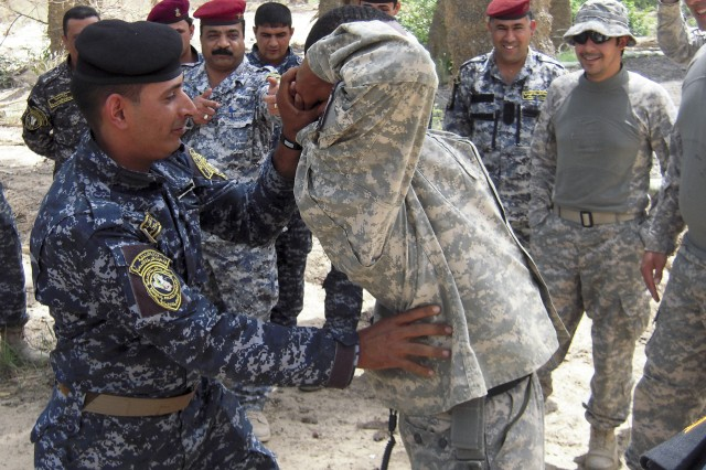 "BAGHDAD— A Soldier of the 1st Mechanized Brigade, 4th Federal Police Division practices how to do a personnel inspection on Staff Sgt. Cedric Wilson of Bandit Troop, 6th ""Saber"" Squadron, 9th Cavalry Regiment, 2nd Advise and Assist Brigade, 1st Infantry Division, United States Division – Center, and a native of Leesville, La., during a traffic control point training program on May 2."