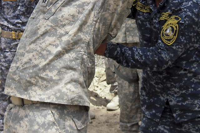 "BAGHDAD— A Soldier of the 1st Mechanized Brigade, 4th Federal Police Division practices how to do a personnel inspection on Cpt. David Hanna of Bandit Troop, 6th ""Saber"" Squadron, 9th Cavalry Regiment, 2nd Advise and Assist Brigade, 1st Infantry Division, United States Division – Center, and a native of Montrose, Colo., during a traffic control point training program on May 2."