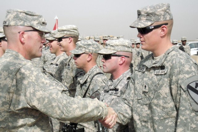 """CAMP LIBERTY, Iraq - Lt. Col. Cameron Cantlon, an Ettrick, Wis., native and commander of 6th """"Saber"""" Squadron, 9th Cavalry Regiment, 2nd Advise and Assist Brigade, 1st Infantry Division, United States Division - Center congratulates Spc. Christian Cowan, a combat medic with A Troop and native of Van Buren, Ark. after awarding him the Combat Medical Badge during a ceremony April 29, 2011 at Camp Liberty, Iraq. The badge, created in 1945 by the War Department, is awarded to Army medics who perform medical duties while engaged by the enemy."""