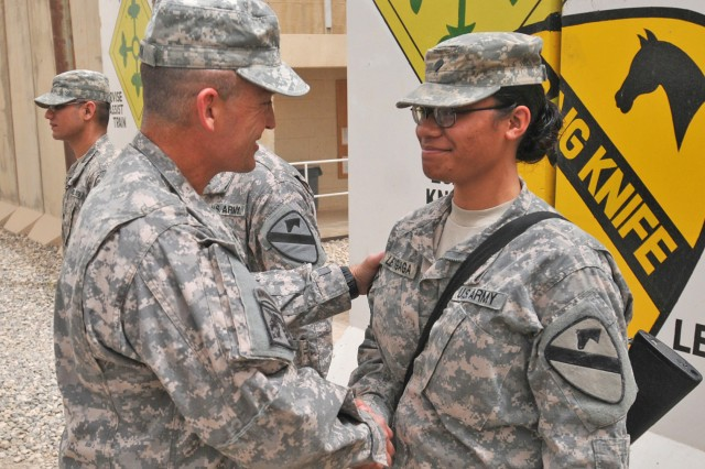 CONTINGENCY OPERATING SITE MAREZ, Iraq - Maj. Gen. Daniel Allyn, commanding general of 1st Cavalry Division, awards Spc. Charis Leatigaga, an administrative clerk assigned to Headquarters and Headquarters Company, 4th Advise and Assist Brigade, 1st Cav. Div., a division coin of excellence for supporting the deployed Fort Hood troopers at Contingency Operating Site Marez, Iraq, during an awards ceremony, May 7, 2011. Allyn visited 4th AAB Soldiers to thank them for their hard work and dedication to the advise, train and assist mission in northern Iraq.