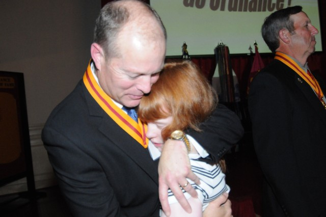 """Retired Sgt. Maj. James W. """"Chip"""" Herrell, wearing his Hall of Fame medallion gets a hug from daughter, Stevie, after his induction."""