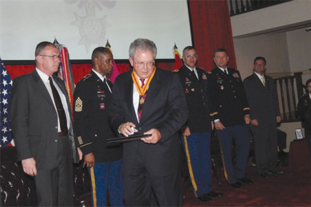 Retired Department of the Army civilian James L. Flinn III accepts his induction certificate and medalion. Flinn was one of three civilians so honored during the Ordnance Corps Hall of Fame Induction Ceremony held May 4 at the Lee Club.