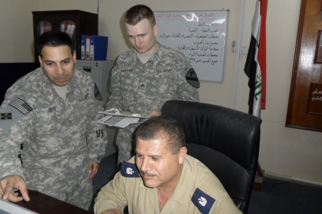 BASRAH, Iraq - Maj. Cruz coordinates Iraqi military escort scheduling with Maj. Amir,   and the Basrah Operations Command noncommisioned officer in charge, Sgt.  Cohen Kanewske.