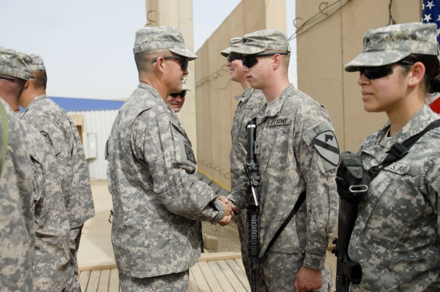 CONTINGENCY OPERATING BASE ADDER, Iraq - Maj. Gen. Daniel Allyn, the commanding general of the 1st Cavalry Division, places a division coin in Spc. Matthew Joseph's hand at a ceremony on Contingency Operating Base Adder, May 6.