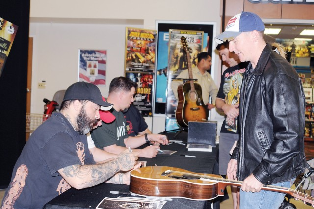 Chief Warrant Officer 3 Bill Kearns, 1st Sqdn., 6th Cav. Regt., CAB, 1st Inf. Div., right, gets his guitar signed by Aaron Lewis, lead singer of the rock band, Staind, and solo country singer, left, during a meet-and-greet April 29 at the Main PX, Fort